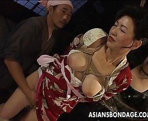 Bound Japanese MILF groans while her cunt is taunted